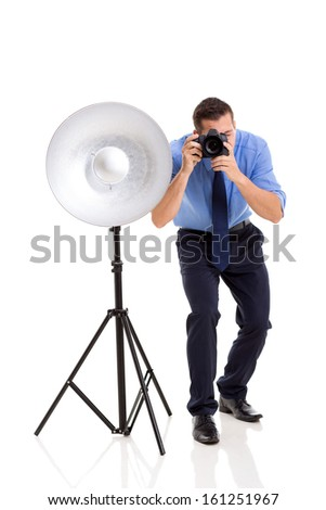 young male photographer working in studio - stock photo