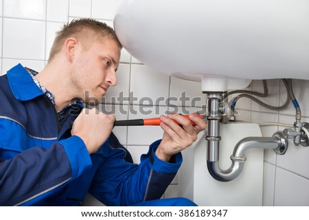 Young Male Plumber Fixing Sink In Bathroom - stock photo