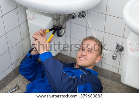 Young Male Plumber Repairing Sink In Kitchen - stock photo