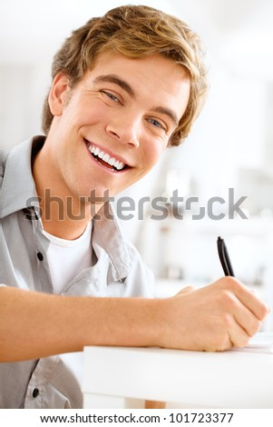 young male professional student is motivated studying at home - stock photo
