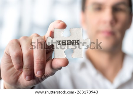 Young male professor holding puzzle piece with word Think in a conceptual image for encouraging you to use your mind and imagination to solve problems and challenges and find solutions in life. - stock photo