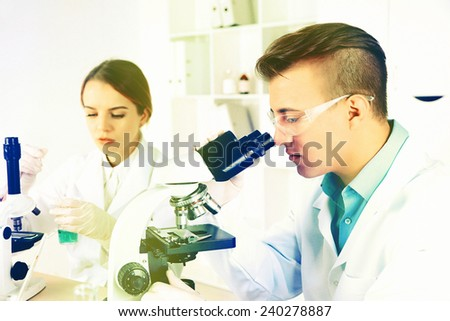Young male researcher carrying out scientific research in lab - stock photo