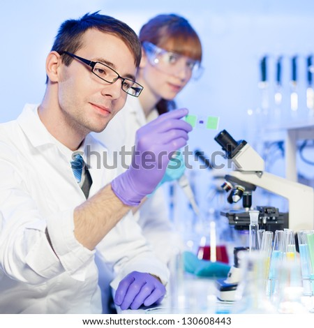 Young male researcher looking at the microscope slide in the life science (forensics, microbiology, biochemistry, genetics, oncology ) laboratory. Female assistant scientist working in the background. - stock photo