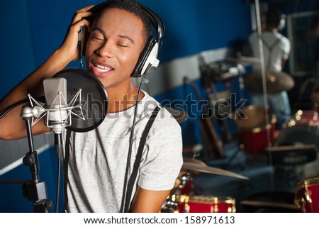 Young male singer in recording studio - stock photo