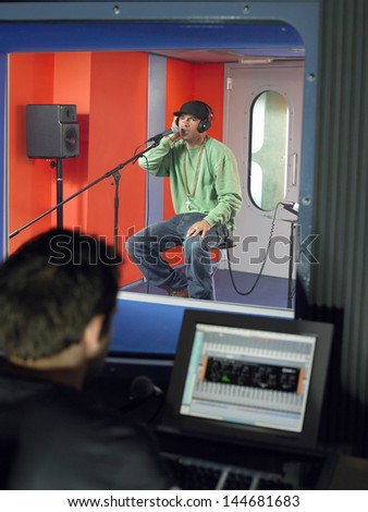 Young male singer with studio technician in foreground at the recording studio - stock photo