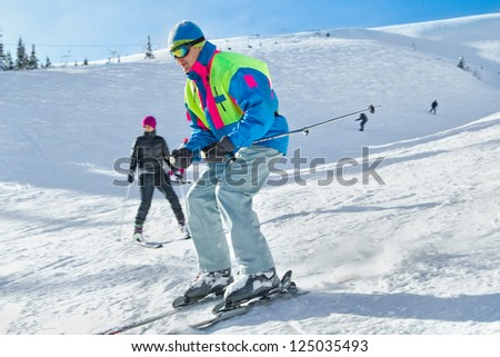 Young male skier turning in powder snow; horizontal orientation - stock photo
