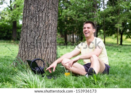 Young male smiling and using laptop in park, spring - stock photo