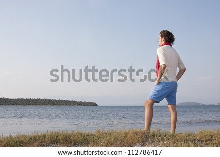 Young male standing at sea side - stock photo