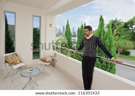 Young male standing on a modern balcony overlooking the city - stock photo