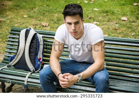 Young Male Student Sitting on the Bench in a Park, next to his Back Pack, While Thinking and Looking Away Seriously. - stock photo