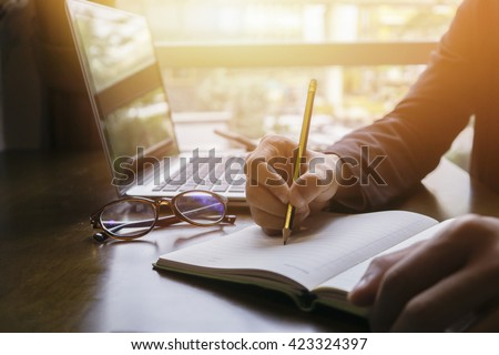 Young male student writes information from portable net-book while prepare for lectures in University campus,hipster man working on laptop computer while sitting in cafe,vintage color,selective focus - stock photo