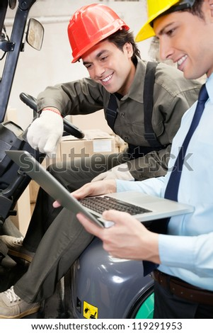 Young male supervisor and forklift driver using laptop at warehouse - stock photo
