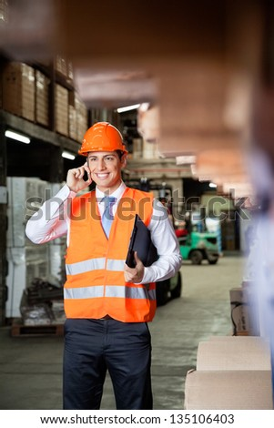 Young male supervisor in orange protective vest using cell phone at warehouse - stock photo