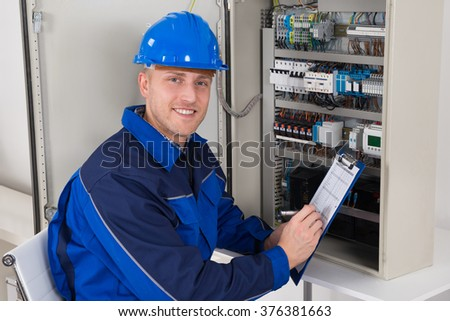 Young Male Technician Holding Clipboard While Examining Fusebox - stock photo
