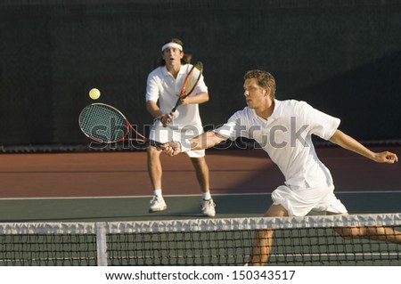 Young male tennis player hitting ball with doubles partner standing in background - stock photo
