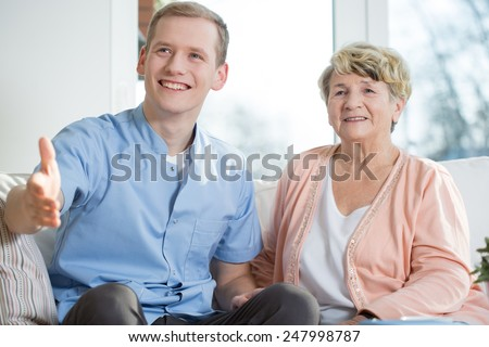 Young male therapist and older lady visiting guests - stock photo