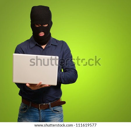 young male thief holding laptop isolated on green background - stock photo