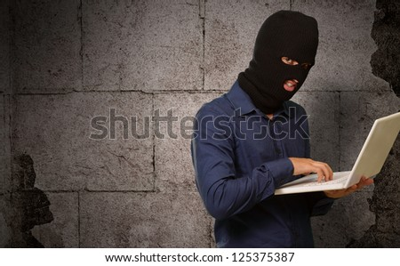 young male thief holding laptop on wall - stock photo