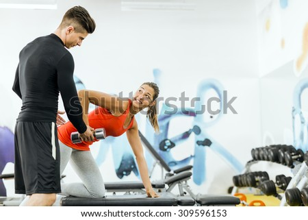 Young male trainer giving instructions to a woman in a gym and being supportive - stock photo
