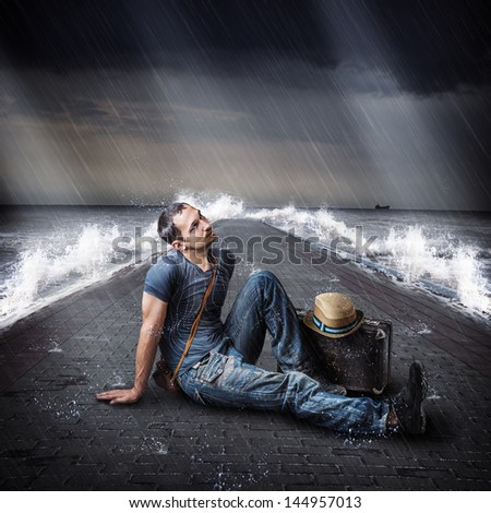 Young male traveler is on the Sea pier during a storm and rain with a suitcase in hand - stock photo