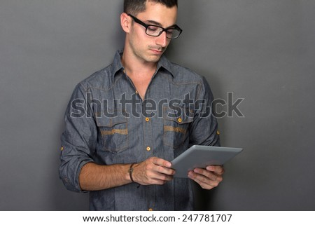 young male using digital tablet against gray background - stock photo