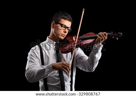 Young male violinist playing an acoustic violin on a black background - stock photo