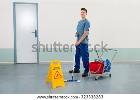 Young Male Worker With Cleaning Equipments Mopping Floor - stock photo