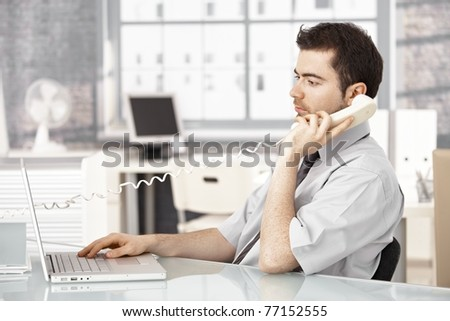 Young male working in bright office, using laptop, talking on phone.? - stock photo
