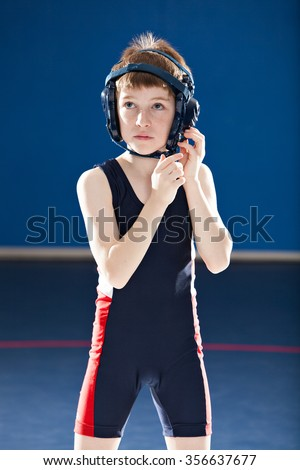 Young male wrestler putting his headgear on - stock photo
