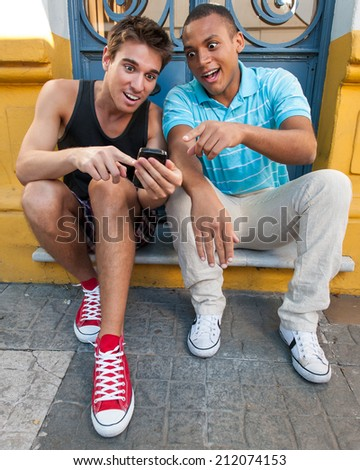 Young males having fun with a cellphone. Outdoors. - stock photo
