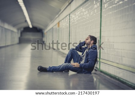 Young man abandoned lost in depression sitting on ground street subway tunnel suffering emotional pain, sadness and looking destroyed and desperate leaning on wall alone  - stock photo