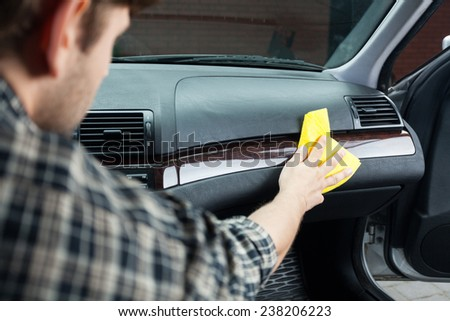 Young man accurately polishing the dashboard in his vehicle - stock photo