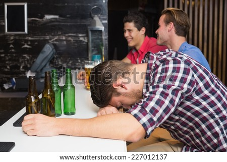 Young man after drinking too much at the bar - stock photo