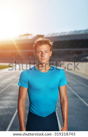 Young man after run standing on outdoor stadium race track. Fit male athlete looking at camera with sun flare. - stock photo