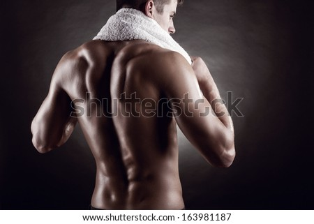 Young man after training on dark background - stock photo