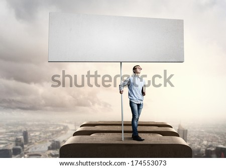 Young man against city background holding blank banner. Place for text - stock photo