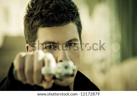 Young man aiming at viewer with a gun - stock photo