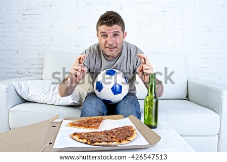 young man alone in stress watching football game on television sitting at home living room sofa couch with ball , pizza box and beer bottle enjoying the match crossing fingers excited - stock photo
