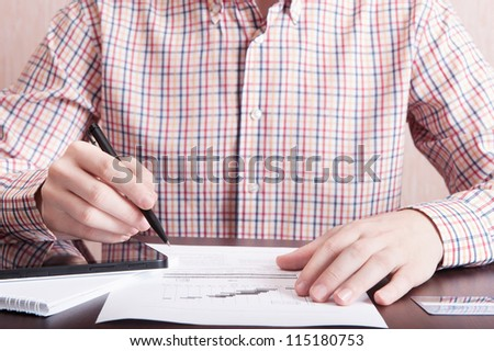 Young man analyze som document with pen in his hand and using tablet PC - stock photo
