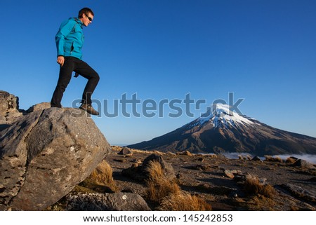 Young man and a volcano - stock photo