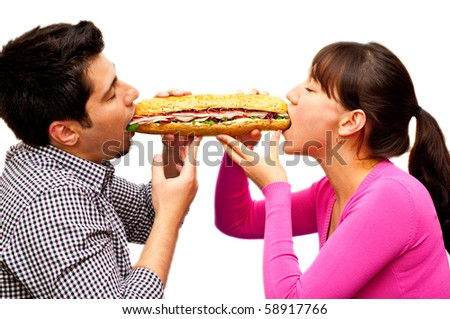 young man and a woman eating sandwich from two sides isolated on white - stock photo