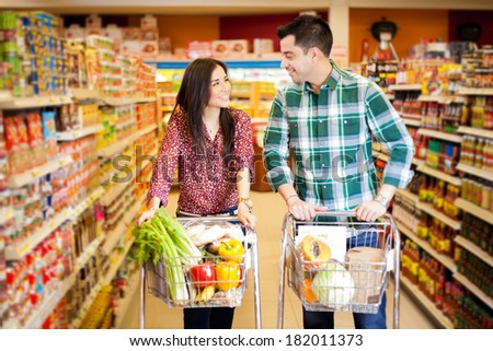 Young man and a woman flirting at the supermarket while they do their shopping - stock photo