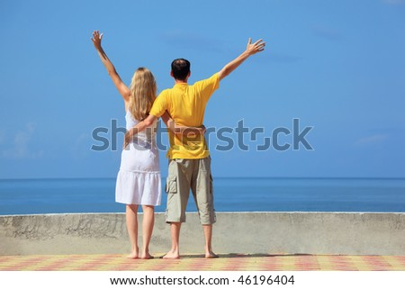 young man and beautiful woman on quay lifted hands upwards - stock photo