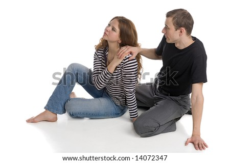 young man and beautiful woman sitting together on white floor background - stock photo