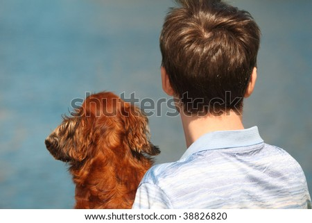 Young man and his dachshund  from back outdoor against water - stock photo
