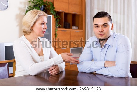 Young man and his mature girlfriend having serious conversation indoors - stock photo