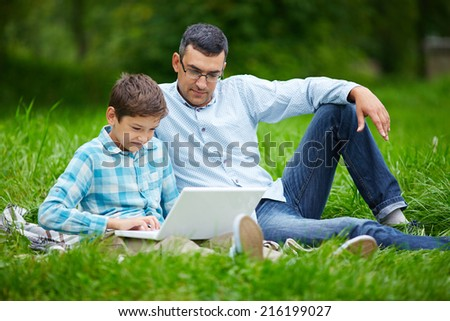 Young man and his son using laptop while relaxing in the park - stock photo