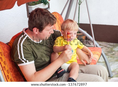 Young man and little baby boy eating colorful ice in summer, outdoors - stock photo