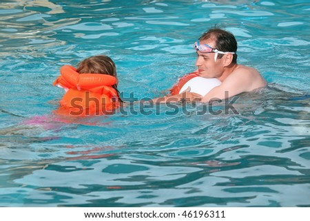 young man and little girl in life-jacket bathing  in pool on resort - stock photo