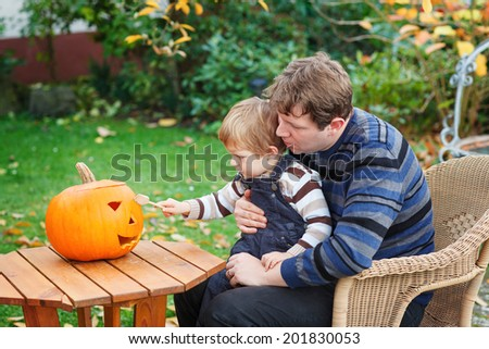 Young man and little toddler boy having fun with making halloween pumpkin face - stock photo